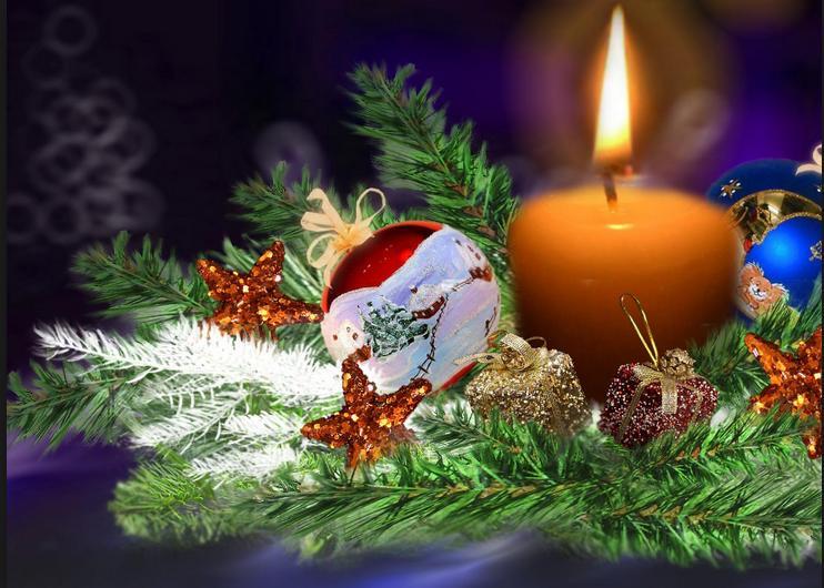 Na stroiku stojąca zapalona świeca i leżąca obok niej bombka
